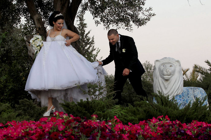 A groom from the Arab Village of Beit Hanina helps his bride with her dress in the Yemin Moshe neighborhood of West Jerusalem as they take photographs before their wedding. Photo by Nati Shohat/Flash90