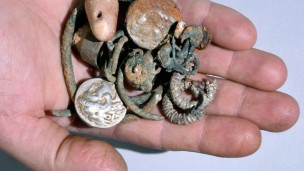 Cache of silver objects: two coins of Alexander of Macedon, rings, bracelets, earrings, and a small stone weight. (Clara Amit, courtesy Israel Antiquities Authority)