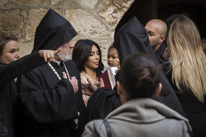 Reality-television star Kim Kardashian, holds her daughter North, as she is greeted by priests at the Saint James Armenian Church in the Armenian Quarter in Jerusalem's Old City. (Photo by Hadas Parush/Flash90)