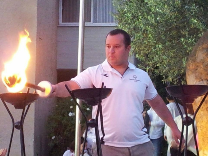 Special Olympics swimming champ Mati Oren lighting an Independence Day torch at Kibbutz Ginegar on April 23, 2015.