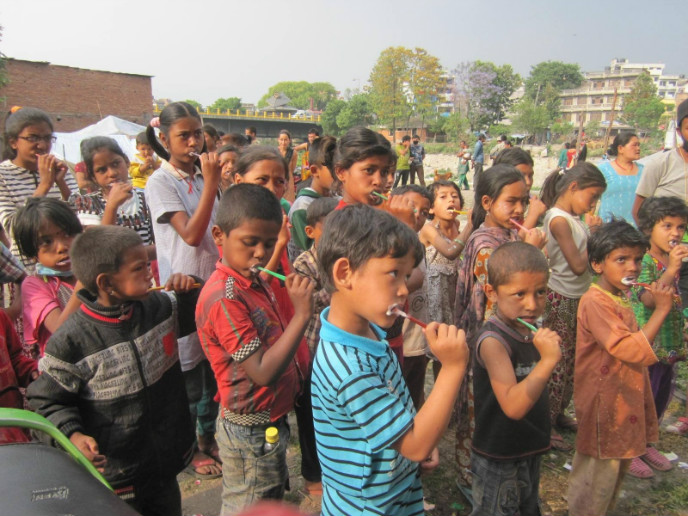 Nepali children using toothbrushes supplied by Tevel b'Tzedek.