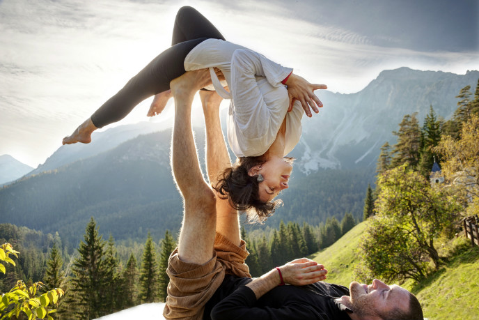 Acro-yoga partners balance, flip and maneuver each other. Image via Shutterstock.com