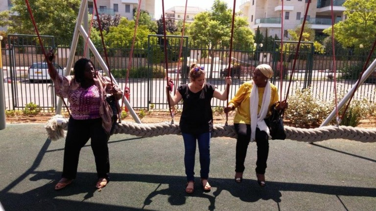 Ayobisi Osuntusa, left, and Fatima Hajju Tomsu Abdul Kadir testing out inclusive playground swings with Beit Issie ShapiroNational Inclusive and Accessible Playground CoordinatorTania Askayo at the original Park Chaverim (Friendship Park).Photo courtesy of Beit Issie Shapiro