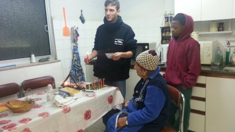 Bakehila youngsters bringing Hanukkah joy to an elderly resident of their community. Photo courtesy of JVP Community