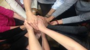 A group of autism professionals link hands during resiliency training. Photo courtesy of ACR