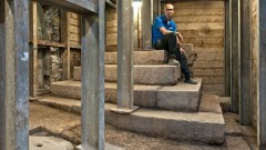 Dr. Joe Uziel, codirector of the excavation from the Israel Antiquities Authority, sitting atop the stepped structure from the Second Temple period. Photo: Shai Halevy; courtesy of the Israel Antiquities Authority.