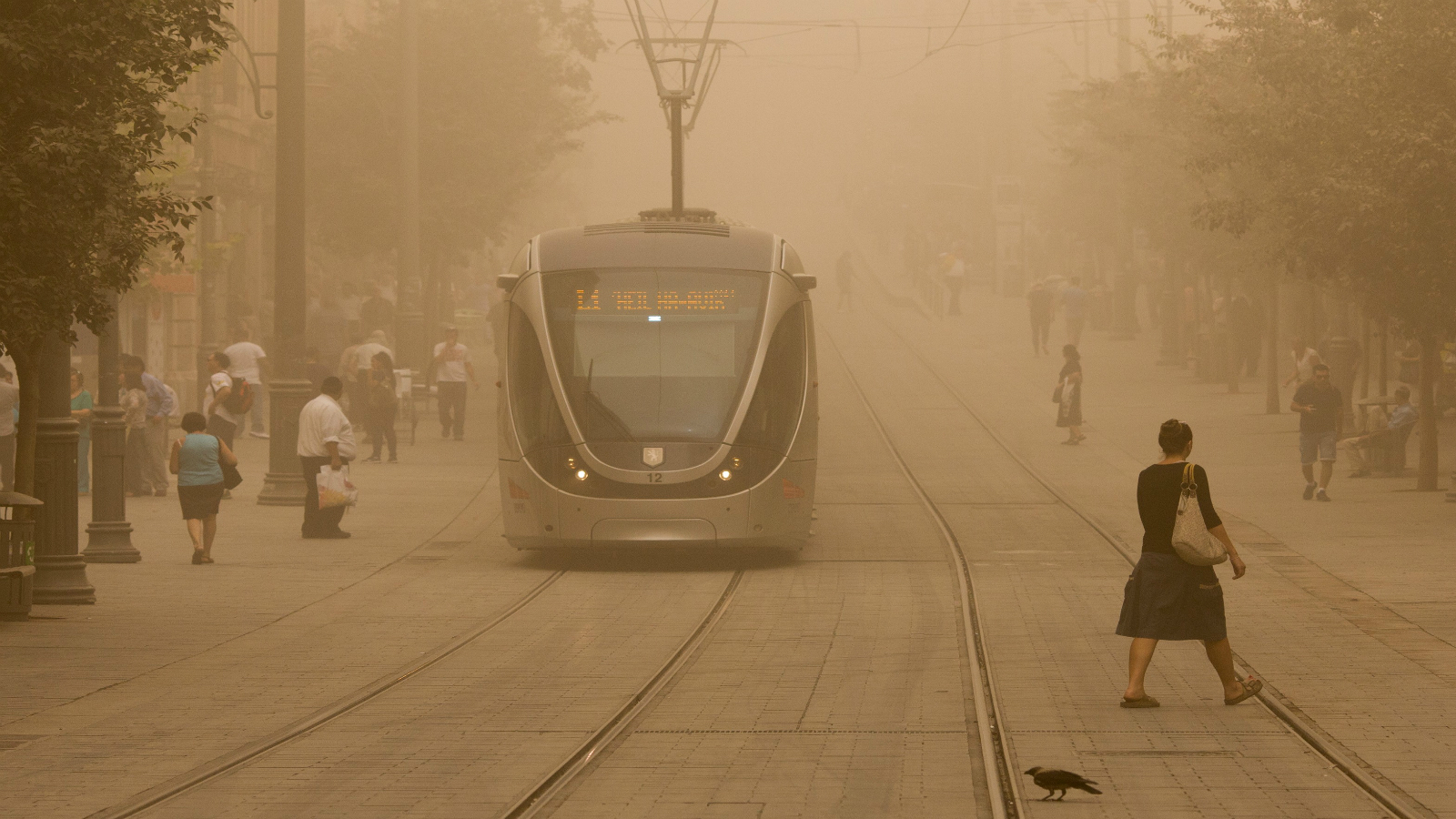 Israelis walk across the light-rail tracks on Jaffa Road in Jerusalem on September 8, 2015, as a sandstorm hit Israel. Photo by Yonatan Sindel/FLASH90