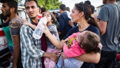 IsraAID volunteer Rachel Lasry Zahavi helping a father care for his daughters during the Hungarian border riot. Photo by Mickey Noam Alon/IsraAID