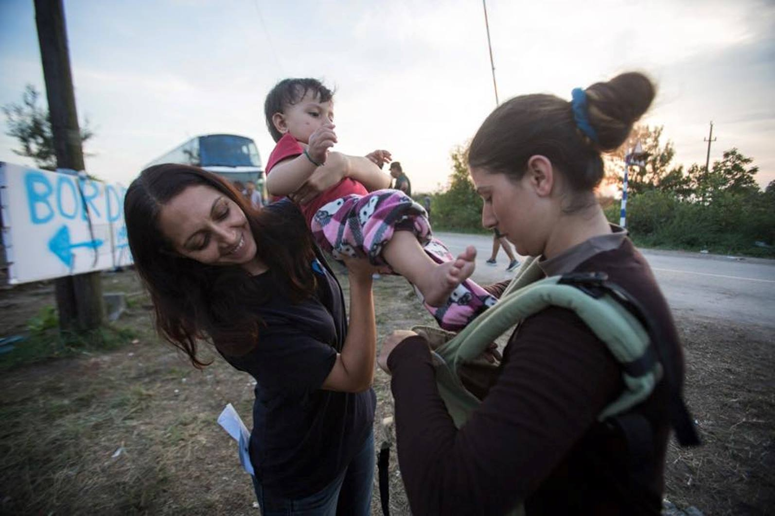 An IsraAID volunteer showing a refugee on the Serbian-Hungarian border how to strap on a baby carrier donated from Israel. Photo via Facebook