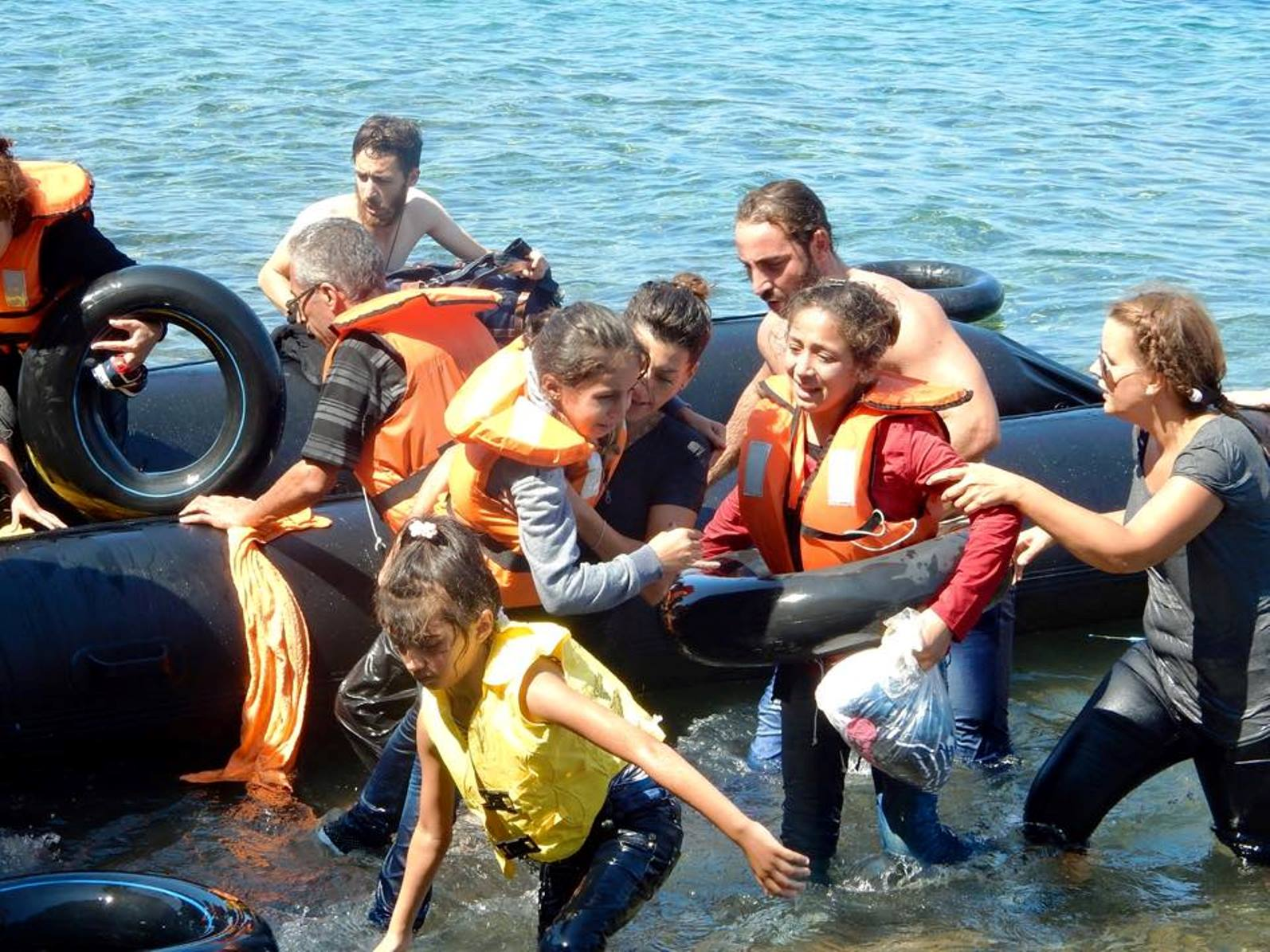 IsraAid volunteers including Naama Gorodischer, center, helping refugees reach the shore after their boat overturned off the Greek coast, September 13, 2015. Photo via Facebook