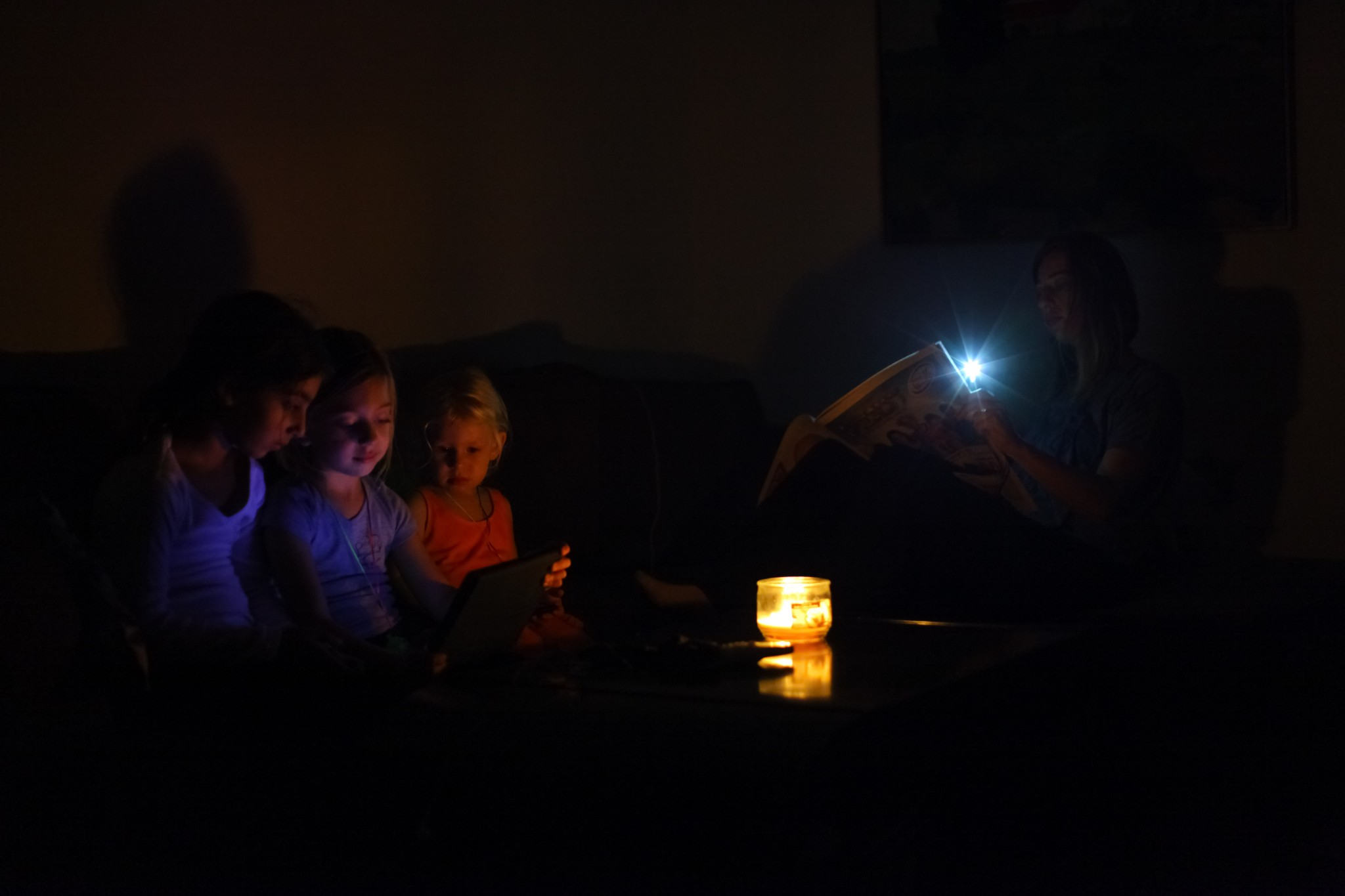 An Israeli family sits in the darkness of their home a day after a powerful rainstorm hit Israel. Photo by Chen Leopold/FLASH90
