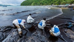 Workers in biohazard suits clean up an oil spill on Ao Prao Beach in Rayong, Thailand in July 2013.  Photo by Narongsak Nagadhana/Shutterstock.com