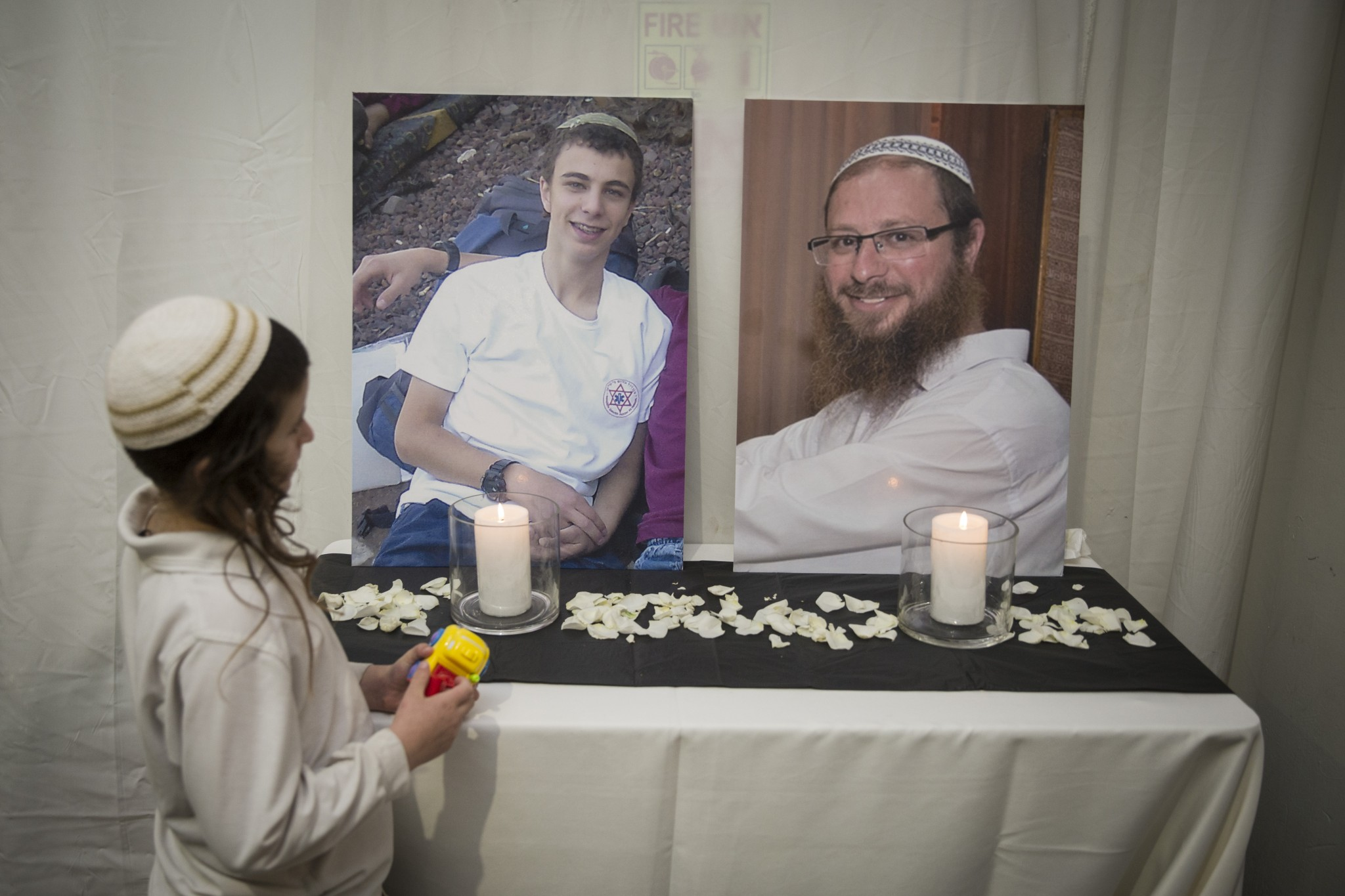 Pictures of Rabbi Yaakov Litman and Netanel Litman, the bride's father and brother, were displayed with memorial candles at her wedding to Ariel Beigel. Photo by Hadas Parush/FLASH90