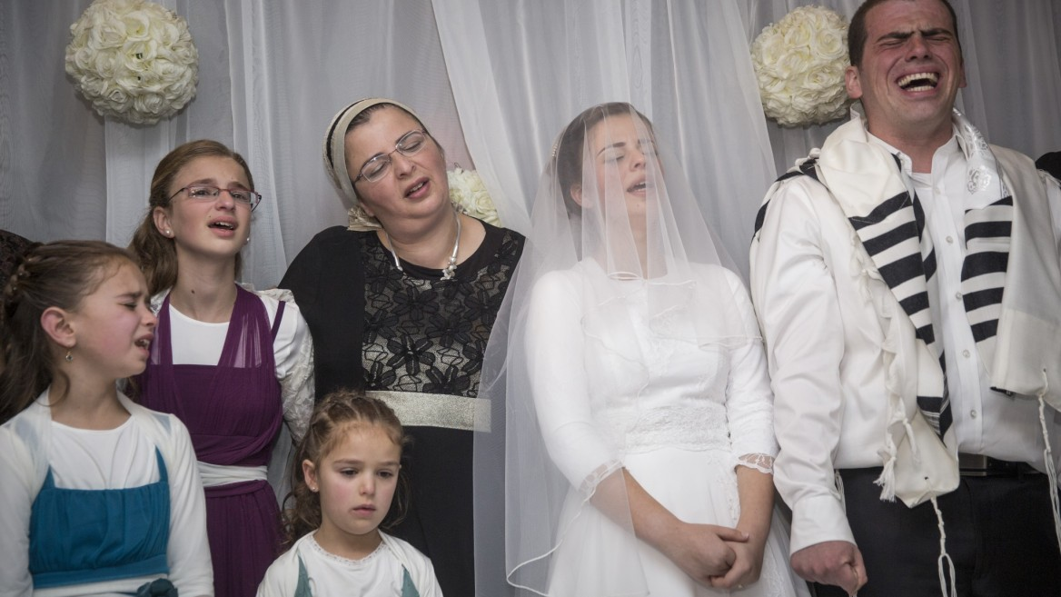 The surviving Litman family singing emotionally with the bride, Sarah-Tehiya Litman, and groom, Ariel Beigel, under the bridal canopy. Photo by Hadas ParushFLASH90
