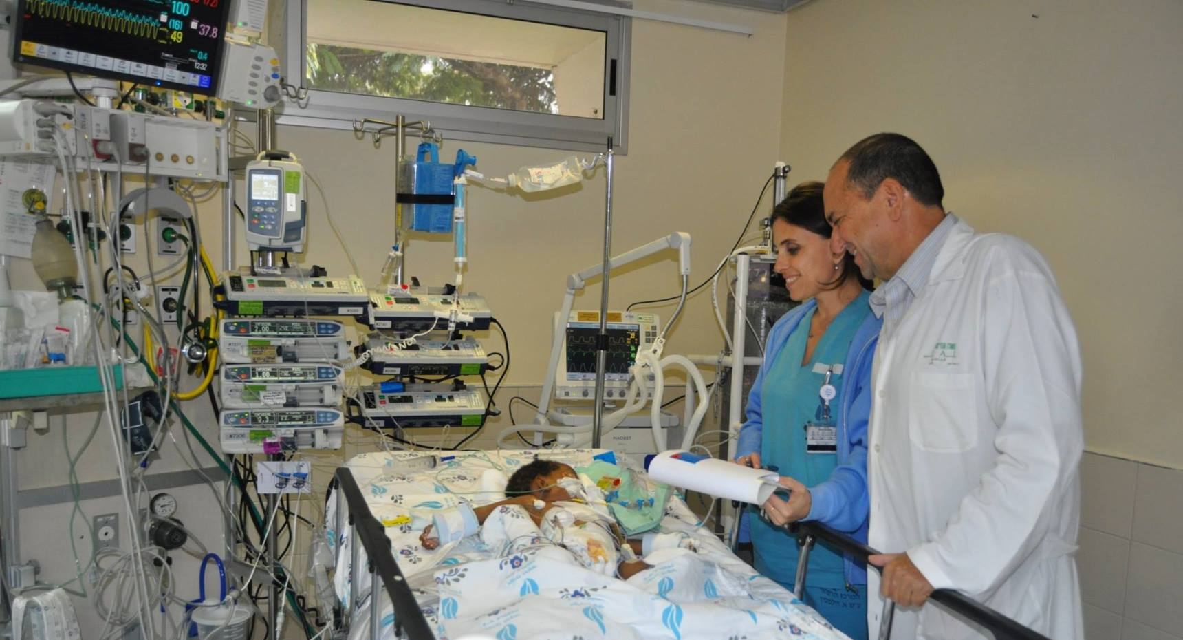 Dr. Sion Houri, head of the pediatric intensive care unit at Wolfson Medical Center, and head nurse Irena Nosel, tending to Dorice. Photo by Rachel Werner