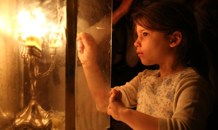 A young girl lights a candle outside her family home in Nachlaot, Jerusalem. Photo by Flash90