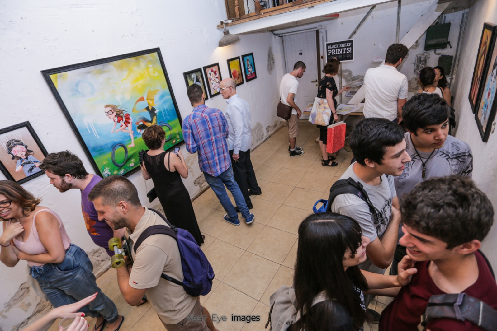 Patrons enjoying street artist Untay's show at Meshuna Gallery in Florentin. Photo by Neat Eye Images