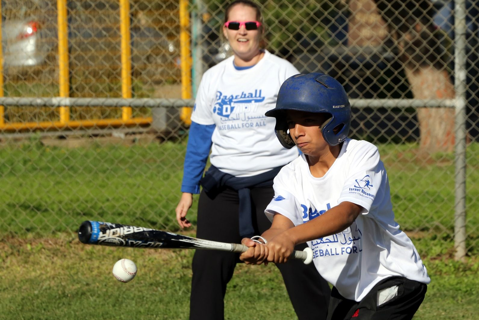 Girls' turn at bat, with Baseball for All official Callie Caughron looking on. Photo by Yossi Zamir/JNF