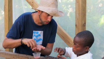 An IsraAID volunteer working with a child of a farm family in the Haiti Grows agricultural training program. Photo: courtesy