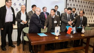 Israeli Robotics Association President Prof. Zvi Shiller, left, at table, shaking hands with officials from China at the MoU signing. Photo by Yair Golov