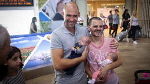 Likud MK Amir Ohana and his partner, Alon Hadad, seen at Ben-Gurion International Airport as they arrive back from the US with their children.  Photo by FLASH90