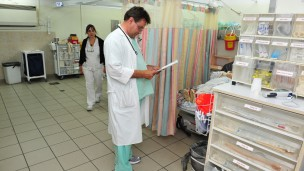 A doctor prepares to examine a patient at hospital. Photo by www.shutterstock.com