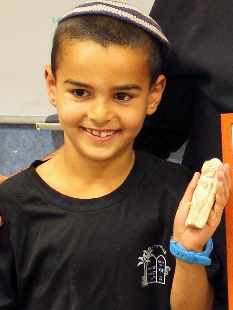 Ori Greenhut and the figurine he found. Photo: Miki Peleg, courtesy of the Israel Antiquities Authority.