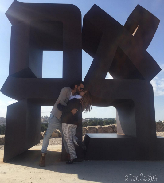 Adamari López and Toni Costa share a kiss at the Love sculpture in Jerusalem. Photo from instagram