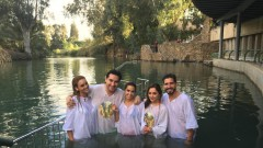 Being baptized in the Jordan River are, from left, Zuleyka Rivera, Luis Alfonso Borrego, Andrea Escalona, Sherlyn González, and Carlitos Perez-Ruiz (Luis Fonsi's manager). Photo courtesy of America's Voices in Israel