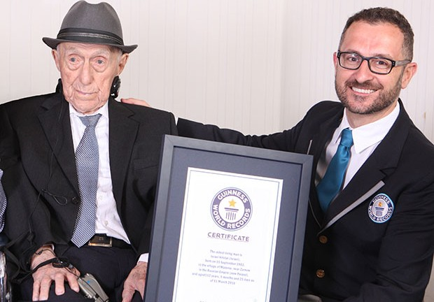 Guinness World Records' Head of Records Marco Frigatti presents Israel Kristal with an official certificate as the world's oldest living man. Photo by Guinness World Records