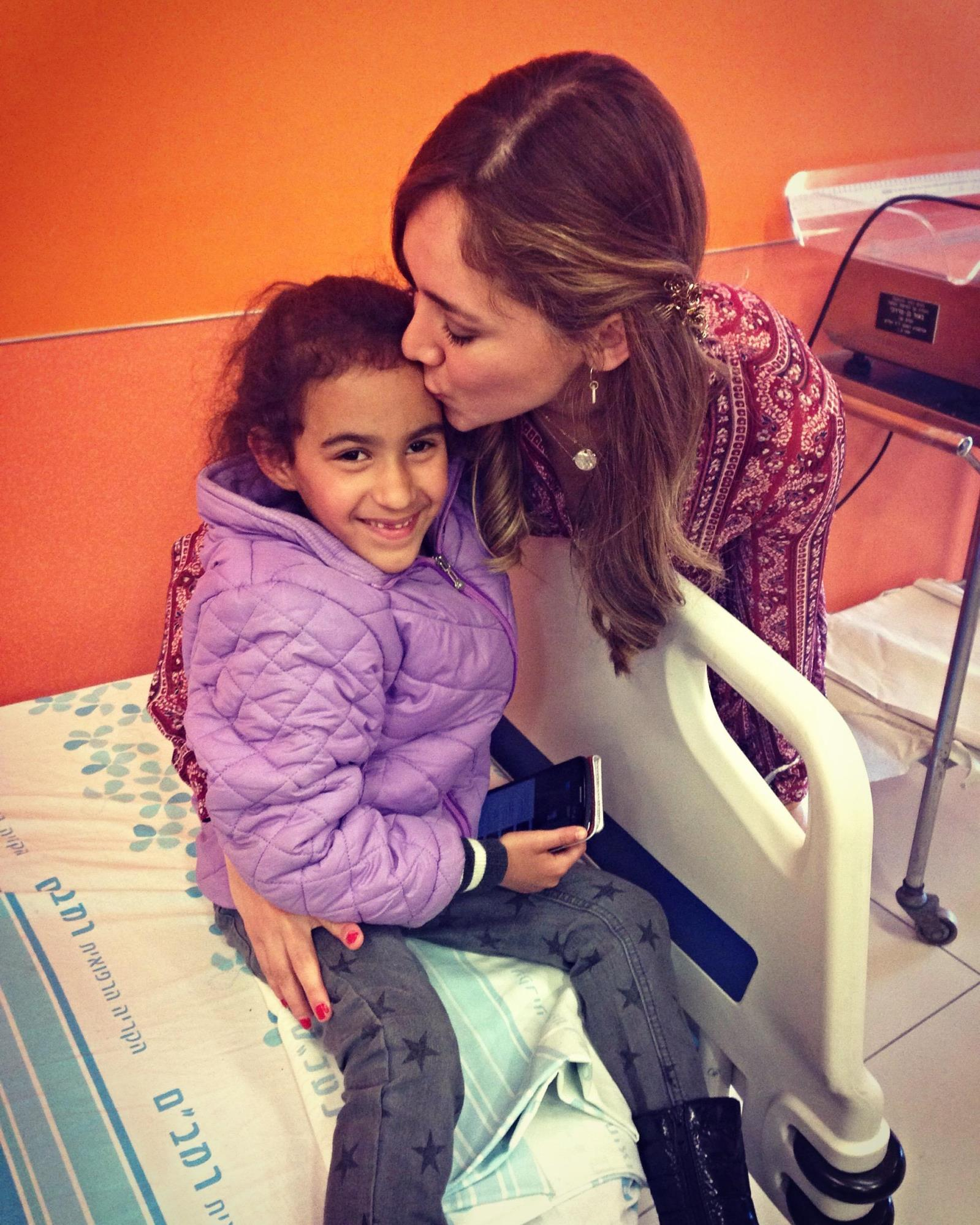 Telenovela actress Sherlyn Gonzalez comforting a young patient at Rambam Health Care Campus. Photo courtesy of America's Voices in Israel