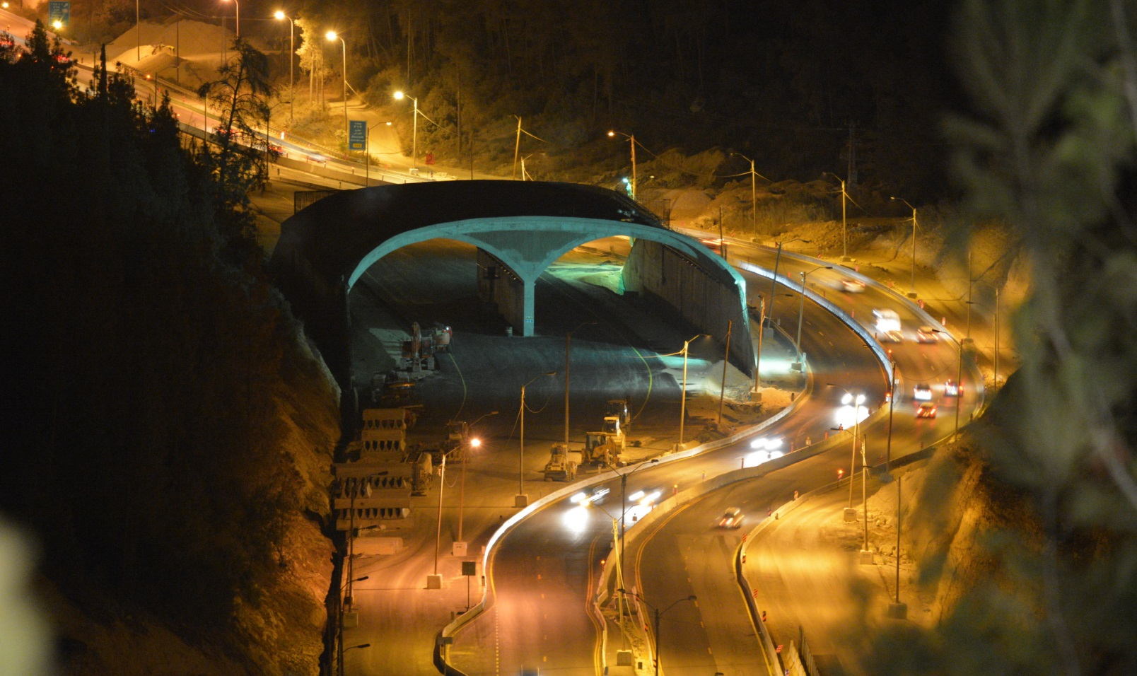 A view of the Highway 1 eco-bridge at night. When the new road is completed, the winding lanes seen to the right will be rerouted under the bridge. Photo courtesy of Netivei Israel