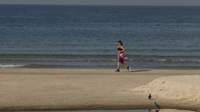 A woman jogs along the beach in Herzliya. Exercise is one of the key ways to reduce sugar levels in the blood. Photo by Flash90