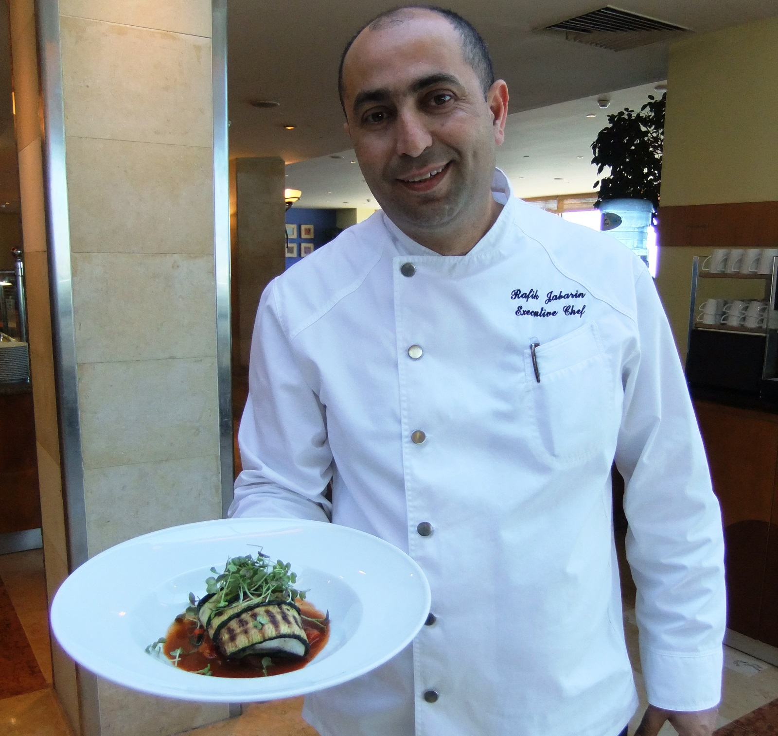 Rafik Jabarin, executive chef of the Tel Aviv Hilton, with his sea bass dish. Photo courtesy of Hilton Worldwide
