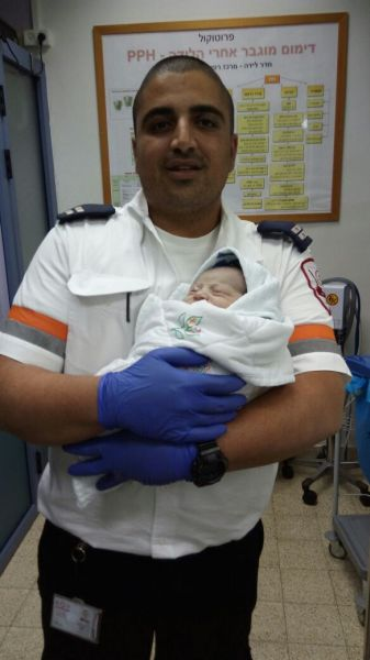 Paramedic Nati Liani with his birthday twin, Baby Boy Sabag. Photo by MDA Spokesman