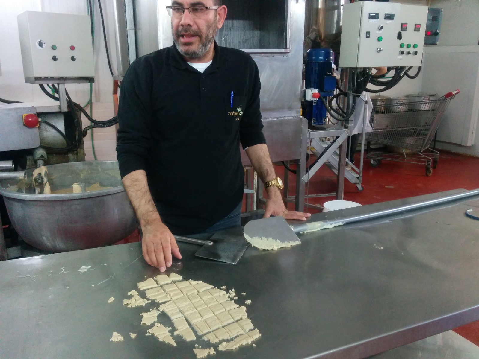 Shafrir Levi slicing freshly made vanilla halva at the Halva Kingdom factory. Photo by Abigail Klein Leichman