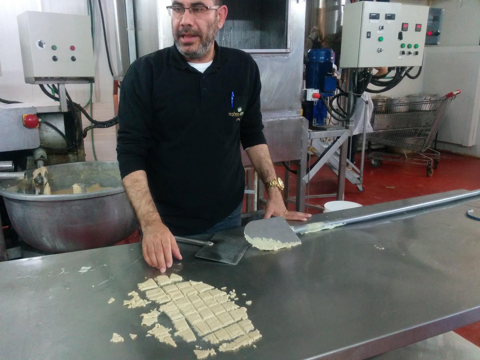 Shafrir Levi slicing freshly made vanilla halva at the Halva Kingdom factory. Photo by Abigail Klein Leichman