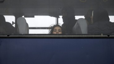 A refugee girl, rescued at open sea, looks through a bus window as she waits to be transferred to the Moria registration centre after arriving at the port of Mytilene on the Lesbos island, Greece, March 22, 2016. REUTERS/Alkis Konstantinidis