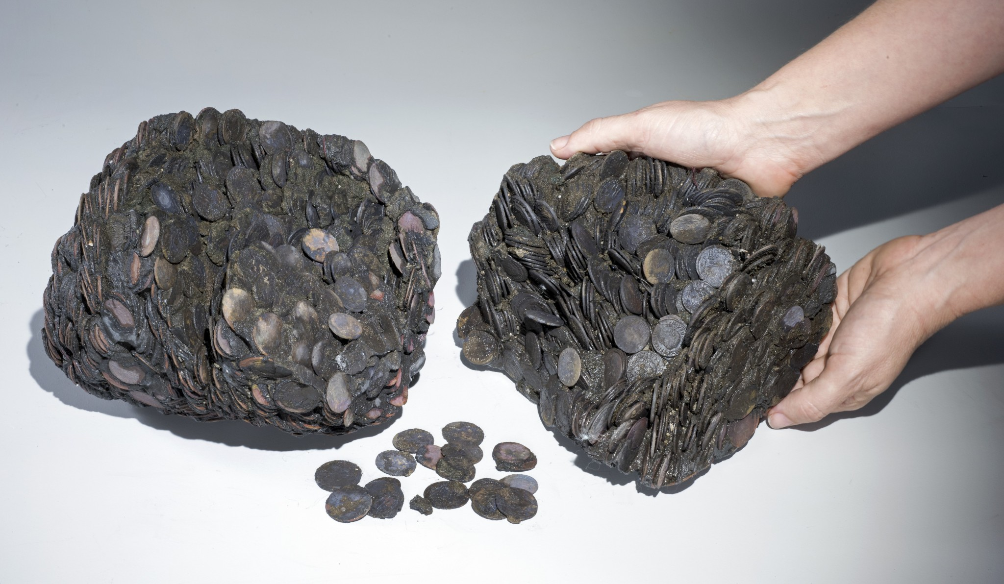 Lumps of coins that were discovered at sea, weighing a total of c. 20 kilograms. Photo by Clara Amit, courtesy of the Israel Antiquities Authority