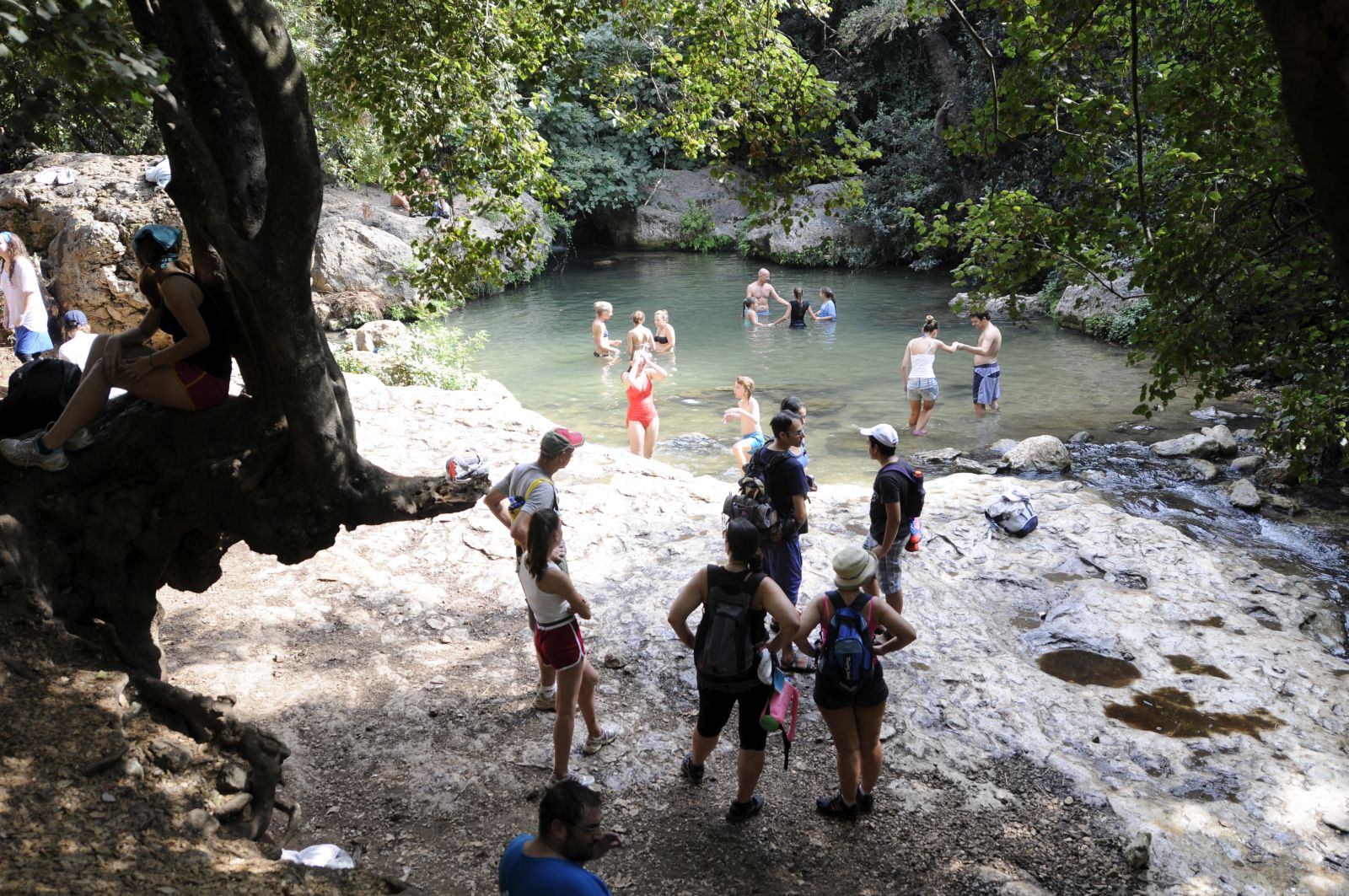 Hikers relax by a spring in the Golan Heights. Photo by Louis Fisher/FLASH90