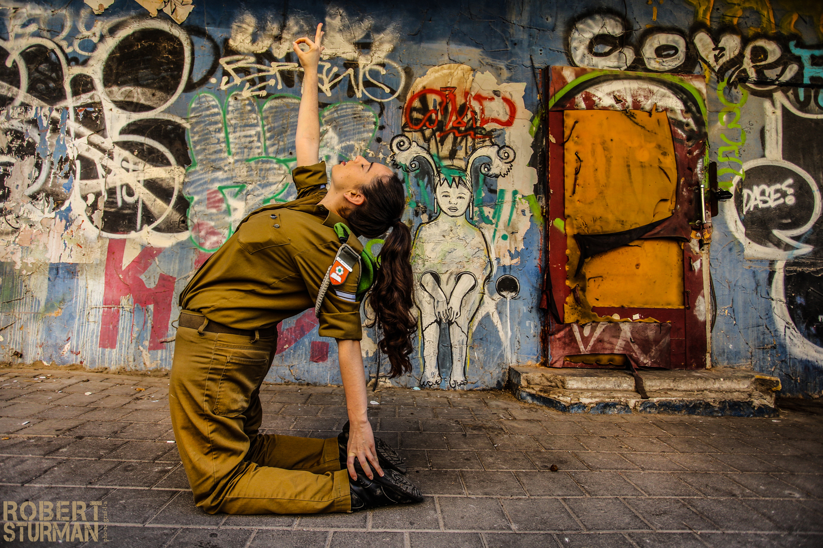 Israeli soldier Mor Gutwillig doing yoga on a Tel Aviv street. Photo by Robert Sturman