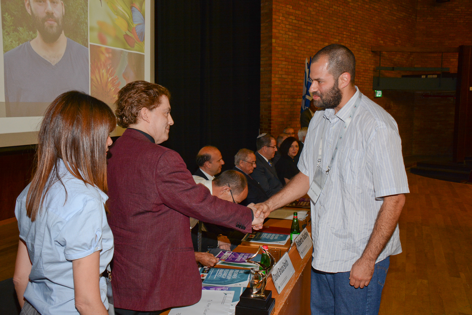 PhD student Alon Cna'ani shaking hands with David Bruce Smith at the award ceremony on June 1, 2016, at the Hebrew University of Jerusalem. Photo by Douglas Guthrie
