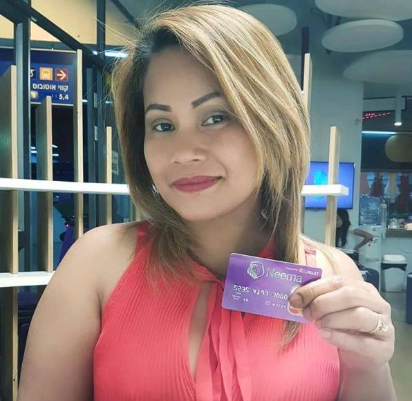 A migrant worker holding her Neema card in Israel. Photo courtesy