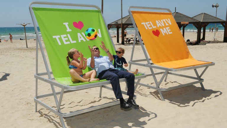 Mayor of Tel Aviv-Yafo Ron Huldai poses with two little helpers on the new lounge chairs on Gordon Beach. Photo by Kfir Sivan