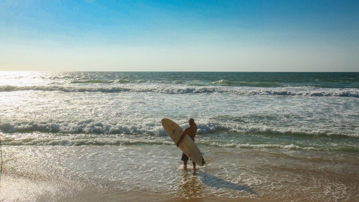 A surfer on the shore of Zikim Beach. Photo by Edi Israel/FLASH90