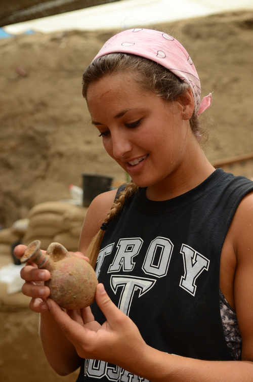A student examines a 10th-9th century BCE juglet in the Philistine cemetery in Ashkelon. Photo by Melissa Aja/Leon Levy Expedition