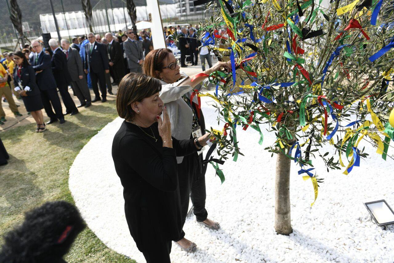Ilana Romano, widow of weightlifter Yossef Romano, and Ankie Spitzer, widow of fencing coach Andrei, add ribbons to a tree at the memorial site in Rio. Photo via Israel Olympic Committee/Facebook