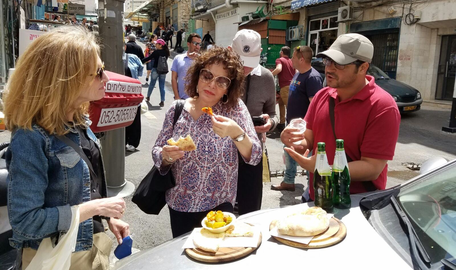In Search of Israeli Cuisine tour guide Avihai Tsabari, right, introducing tourists to Georgian dishes acharuli and ameruli from Khachapuria restaurant in Jerusalem's Machane Yehuda marketplace. Photo: courtesy