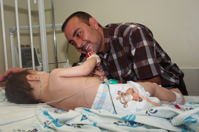 A Yazidi child, Wisam, and his dad at Wolfson Medical Center following heart surgery. Photo courtesy of SACH