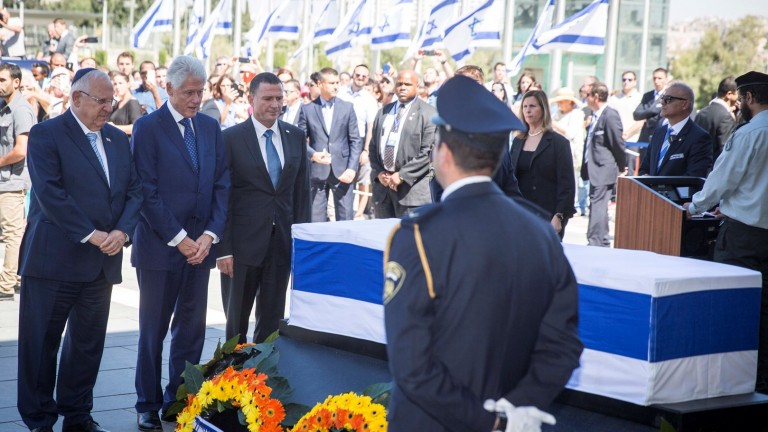 Former US President Bill Clinton, flanked by Israeli President Reuven Rivlin, left, and Knesset Speaker Yuli Edelstein, pays his respects by the coffin of former Israeli President Shimon Peres on the Knesset square in Jerusalem, September 29, 2016. Photo by Hadas Parushl/FLASH90